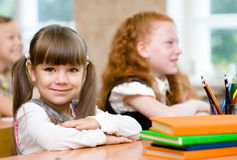 Petite fille s'asseyant et étudiant à la classe d'école photographie stock libre de droits