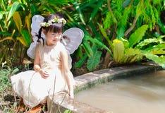Petite fille s'asseyant jouant l'eau avec le dos d'aile dessus Photographie stock libre de droits