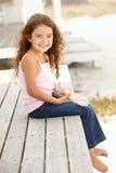 Petite fille s'asseyant à l'extérieur retenant des étoiles de mer Photos stock