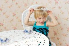 Petite fille s'asseyant près d'un hublot Images stock