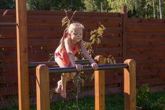 Petite fille s'asseyant sur des barres parall?les dehors photos stock