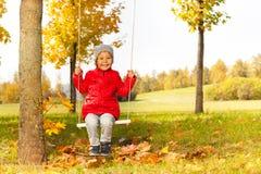 Petite fille s'asseyant sur des oscillations et souriant heureusement Image stock