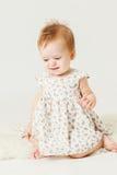 Petite fille s'asseyant sur l'habillement du mouton Image stock