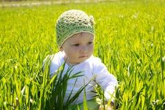 Petite fille s'asseyant sur l'herbe Image stock