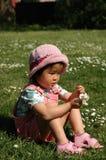 Petite fille s'asseyant sur l'herbe Photos libres de droits