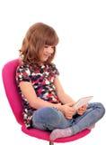 Petite fille s'asseyant sur la chaise et le jeu avec le PC de comprimé Photographie stock libre de droits