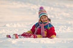 Petite fille s'asseyant sur la neige Image libre de droits