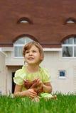 Petite fille s'asseyant sur la pelouse devant la maison neuve Photographie stock libre de droits