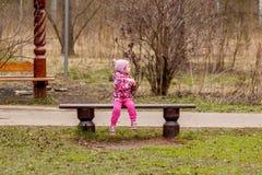 Petite fille s'asseyant sur le banc Images libres de droits