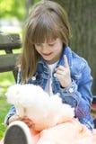 Petite fille s'asseyant sur le banc et les jeux avec son stu préféré Photos libres de droits