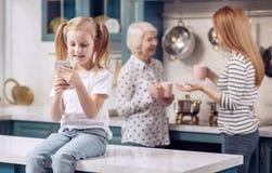 Petite fille s'asseyant sur le compteur et jouant au téléphone Photo libre de droits