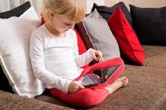 Petite fille s'asseyant sur le divan avec le comprimé dans son recouvrement Image stock
