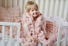 Petite fille s'asseyant sur le lit avec un plaid géant tricoté Photographie stock libre de droits
