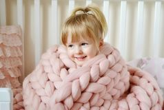 Petite fille s'asseyant sur le lit avec un plaid géant tricoté Photos stock