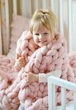 Petite fille s'asseyant sur le lit avec un plaid géant tricoté Images libres de droits