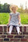 Petite fille s'asseyant sur le mur, heureux d'être aux pieds nus Image stock