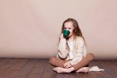 Petite fille s'asseyant sur le plancher et le thé potable photos libres de droits