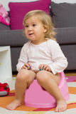 Petite fille s'asseyant sur le pot Photo stock