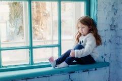 Petite fille s'asseyant sur le rebord de fenêtre près de la fenêtre Photos stock
