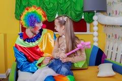 Petite fille s'asseyant sur le recouvrement d'un clown gai Photo libre de droits