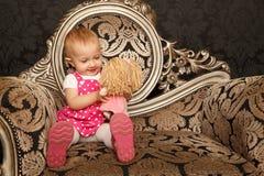 Petite fille s'asseyant sur le rétro fauteuil avec la poupée Images stock
