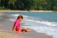 Petite fille s'asseyant sur le sable photographie stock