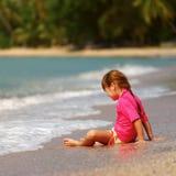 Petite fille s'asseyant sur le sable images stock