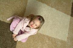 Petite fille s'asseyant sur le tapis Photographie stock libre de droits