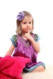 Petite fille s'asseyant sur le tapis avec le manteau de fourrure Photographie stock libre de droits