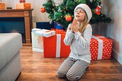Petite fille s'asseyant sur ses genoux et prière Elle maintient des yeux togther fermée et de prises de mains Enfant souhaitant e images libres de droits