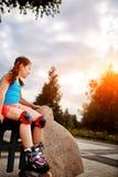 Petite fille s'asseyant sur un banc dans les patins de rouleau de port de parc de ville dans le jour d'été chaud Images stock