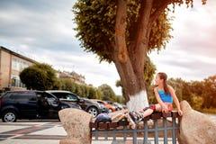 Petite fille s'asseyant sur un banc dans les patins de rouleau de port de parc de ville dans le jour d'été chaud Photos stock
