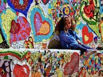 Petite fille s'asseyant sur un banc de mosaïque de coeur en parc Images stock