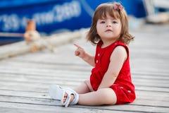 Petite fille s'asseyant sur un pilier en bois Image libre de droits