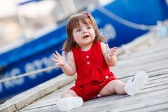 Petite fille s'asseyant sur un pilier en bois Images libres de droits