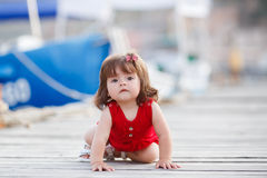 Petite fille s'asseyant sur un pilier en bois Photos libres de droits