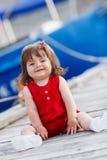 Petite fille s'asseyant sur un pilier en bois Images stock