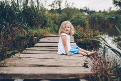 Petite fille s'asseyant sur un pilier en bois Photos stock
