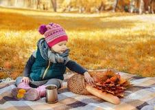 Petite fille s'asseyant sur un plaid images stock
