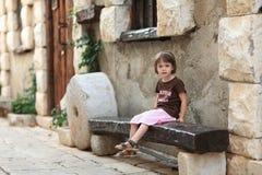 Petite fille s'asseyant sur un vieux banc en bois Image stock