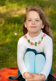 Petite fille s'asseyant sur une pelouse Images libres de droits