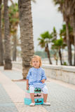 Petite fille s'asseyant sur une pile de valises Photographie stock libre de droits
