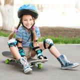 Petite fille s'asseyant sur une planche à roulettes Image libre de droits