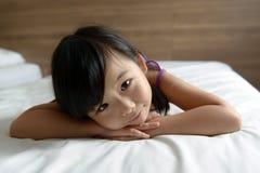 Petite fille s'étendant sur le lit Image libre de droits