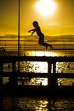 Petite fille sautant dans la mer Photographie stock libre de droits