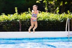 Petite fille sautant dans la piscine Image stock