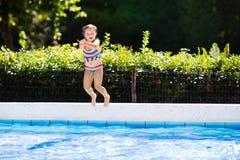 Petite fille sautant dans la piscine Photo stock