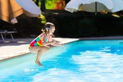 Petite fille sautant dans la piscine Images stock