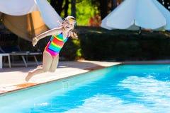 Petite fille sautant dans la piscine Images libres de droits