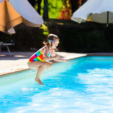 Petite fille sautant dans la piscine Photos stock